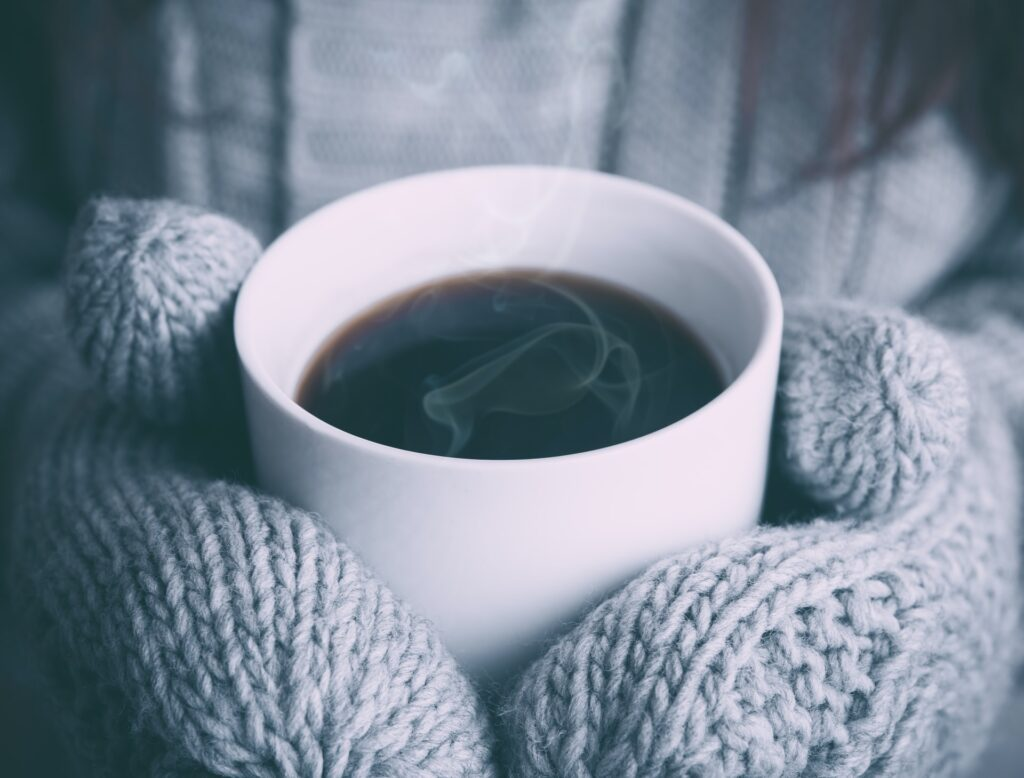 someone wearing mittens and holding a cup of coffee